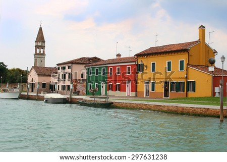 Colorful fishermens houses along the shore  with it's tilted church bell tower of the Italian island of Burano - stock photo