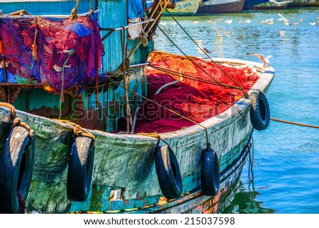 Colorful fishing boat with two seagulls sitting on the sideboard and several other seagulls flying above the water in the background - stock photo