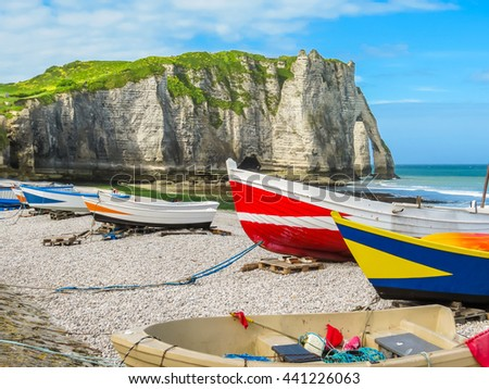 Colorful fishing boats ashore of English Channel and cliff Porte d'Aval as background. Etretat, Normandy, France