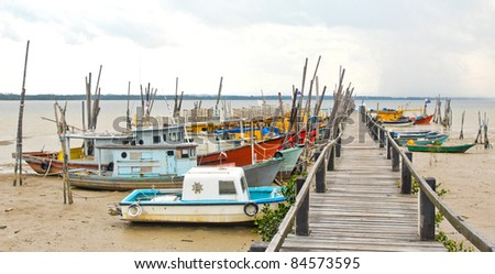 Colorful Fishing Boats at Pier at Low Tide, in Malaysia - stock photo