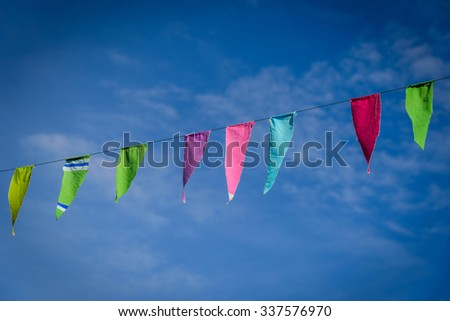 Colorful flag flying on blue sky background - stock photo