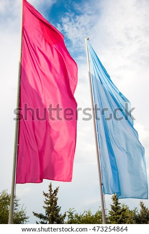 Colorful flags are swaying in the breeze on a summer day