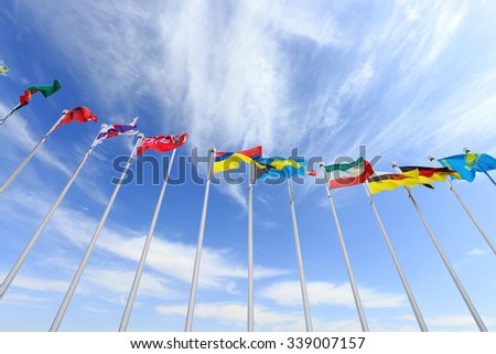 colorful flags in blue sky with clouds