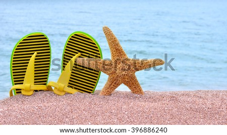 Colorful flip flops and starfish on the beach. - stock photo