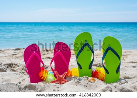 colorful flip flops by the sea in Sardinia, Italy - stock photo