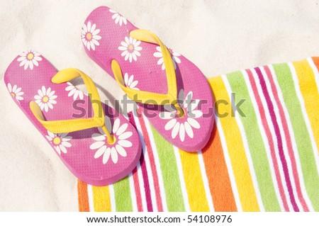 colorful flip flops on beach towel - stock photo