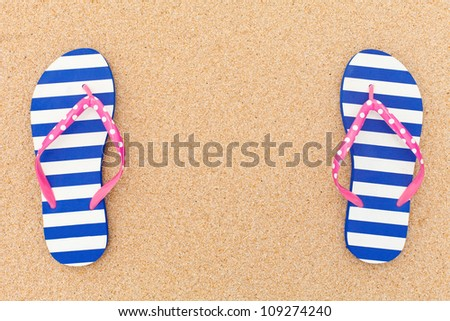 Colorful flipflop pair as a frame on beach sand - stock photo