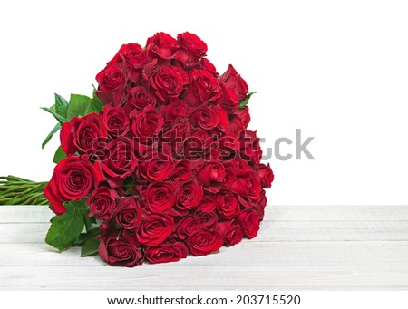 Colorful flower bouquet from red roses isolated on wooden background. Closeup.