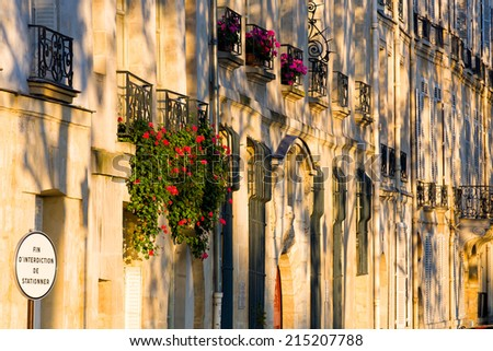 Colorful flowers against a typical row of windows of quaint houses along the river Seine bank in Paris, capital of France - stock photo