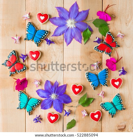 Colorful flowers and homemade butterfly shaped cookies floral composition with copy space  on cedar wood table. Top view.