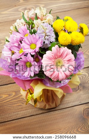 Colorful flowers bouquet on wooden table - stock photo