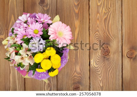 Colorful flowers bouquet on wooden table. Top view with copy space - stock photo