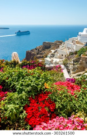 Colorful flowers, buildings and cruise ship on the sea in Oia town, Santorini island, Greece