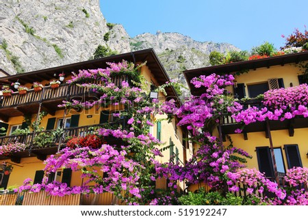 Colorful flowers decorating old houses, Limone sul Garda, Lake Garda, Italy. Beautiful summer day by one of the most popular lakes in Italy. European vacation, popular travel and honeymoon destination