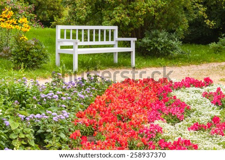 Colorful flowers on the flowerbed in summer park. White wooden bench on the background. Selective focus. Trigorskoye village, Russia - stock photo