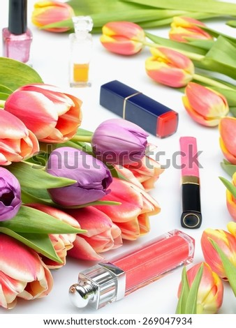Colorful flowers tulips and items of makeup and cosmetics for women on a white background - stock photo