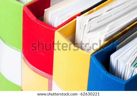 Colorful folders full of papers upper view - stock photo