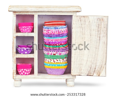 Colorful forms to make cupcakes from paper on a wooden box isolated - stock photo