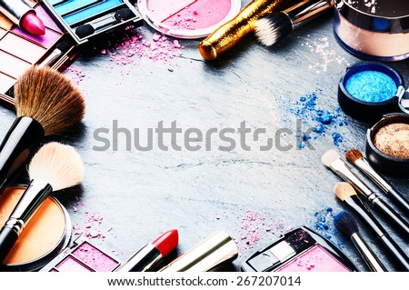 Colorful frame with various makeup products on dark background - stock photo