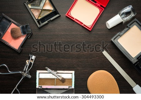 Colorful frame with various makeup products on dark background with copy space - stock photo