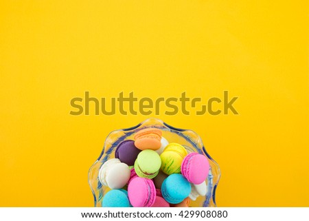 Colorful france macarons on yellow background - stock photo