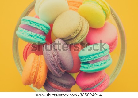 Colorful france macarons on yellow background - Vintage filter effect - stock photo