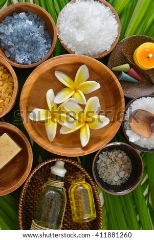 colorful frangipani with oil, salt in wooden bowl on palm