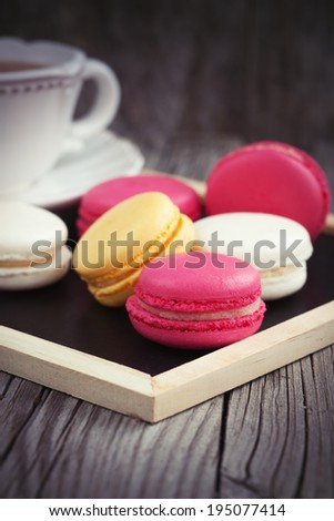 Colorful French macaroons on a dark rustic wooden background, selective focus