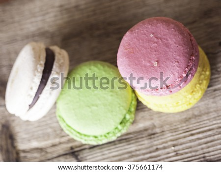 Colorful French macaroons on a dark  wooden background top view - stock photo