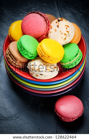 Colorful French macaroons on multicolor plate stack - stock photo