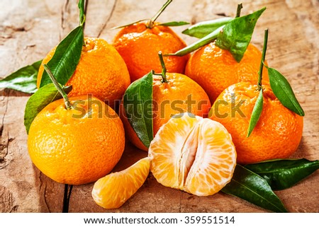 Colorful fresh clementine, mandarin or tangerines on a rustic wooden table with juicy peeled segments in the foreground - stock photo