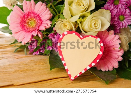 Colorful fresh  flowers bouquet  isolated on wood  background and heart shaped card. - stock photo
