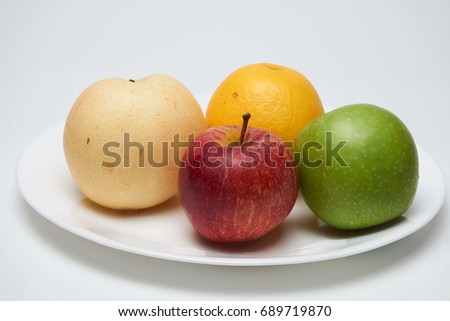Colorful fresh fruits on white plate isolated on white background.