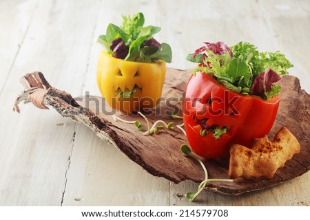 Colorful fresh Halloween bell pepper salads in individual servings for appetizers with carved jack-o-lantern faces stuffed with leafy green lettuce and herbs served on a bark platter with a bat cookie - stock photo