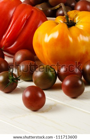 Colorful fresh heirloom tomatoes shown on a rustic white table