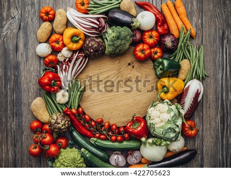 Colorful fresh organic vegetables composing a frame on a rustic chopping board, cooking and healthy eating concept