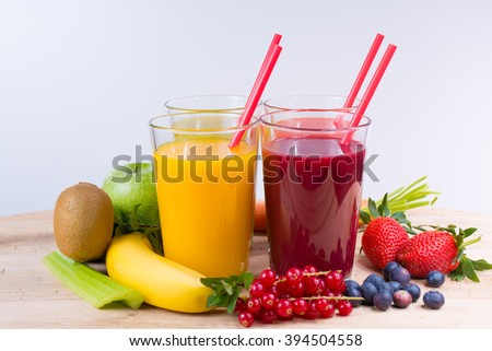Colorful fresh pressed fruit green, yellow, orange and red juices with fresh fruits and berries on white background