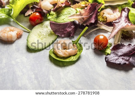 Colorful fresh salad with cucumber and shrimps, close up, place for text - stock photo