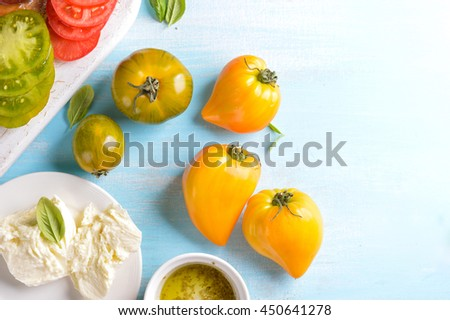 Colorful fresh tomatoes, cheese and pesto, selective focus. Cooking course poster background - layout with free text space. - stock photo