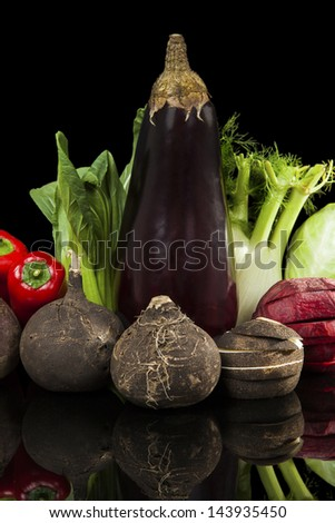 Colorful fresh vegetable background. Beet, capsicum, fennel, aubergine and radish isolated on black background. Healthy vegetarian and vegan eating. - stock photo
