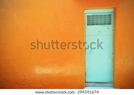 Colorful front door on the wall. Textured background. Pastel color. Vintage effect.
