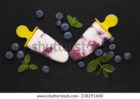 Colorful fruit ice lolly background. Two popsicle on black background with fresh berry fruit and green leaves, top view. Fresh fruit background. - stock photo