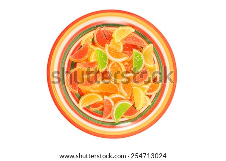 colorful fruit jelly candies on dish isolated on white background - stock photo