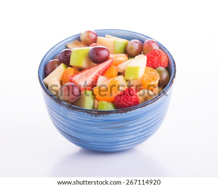 Colorful fruit salad in a blue ceramic bowl, on light background - stock photo