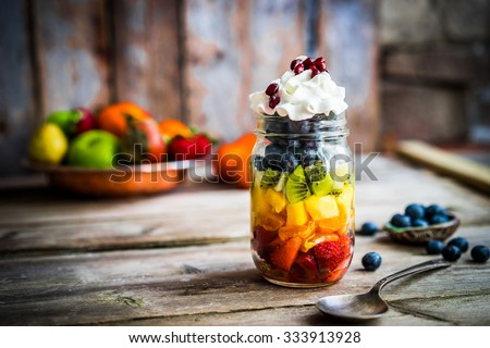 Colorful fruit salad in a jar on rustic wooden background - stock photo