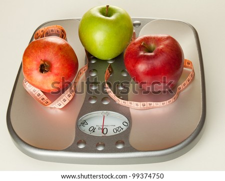 Colorful fruits with measuring tape on a silver scale