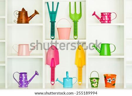colorful gardening tools on white shelf - fork, shovel, rake, bucket, watering can  - stock photo