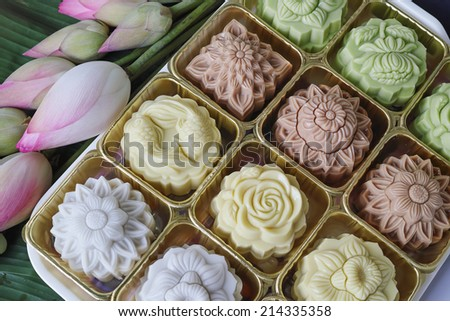Colorful Gelatin Jelly Mooncake ( Banh Trung Thu Rau Cau ) with lotus flowers on green banana leaf - stock photo