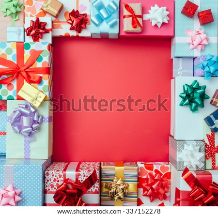 Colorful gift boxes framing a red blank copy space on a desktop, top view, Christmas and celebrations concept - stock photo