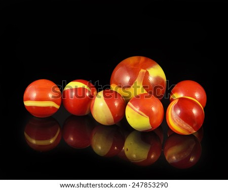 Colorful glass balls for children to play on black background - stock photo